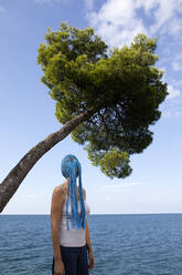 Woman wearing crocheted blue headdress with fringes standing in front of the sea looking up - PSTF00685