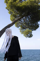 Woman wearing crocheted white headdress with fringes standing in front of the sea - PSTF00688