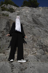 Woman dressed in black wearing crocheted white headdress with fringes standing in front of rock face - PSTF00691