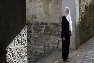 Woman dressed in black wearing crocheted white headdress with fringes, Rovinj, Croatia - PSTF00694
