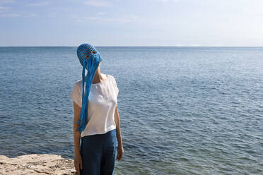 Woman wearing crocheted blue headdress with fringes standing in front of the sea - PSTF00697