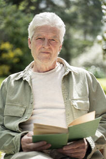 Portrait of senior man reading book while sitting in back yard on sunny day - AFVF06184