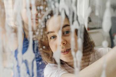 Portrait of teenage girl looking through wet windowpane - OGF00305