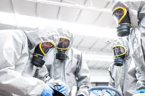 Low angle view of sanitation workers preparing for decontamination in warehouse - JCMF00665