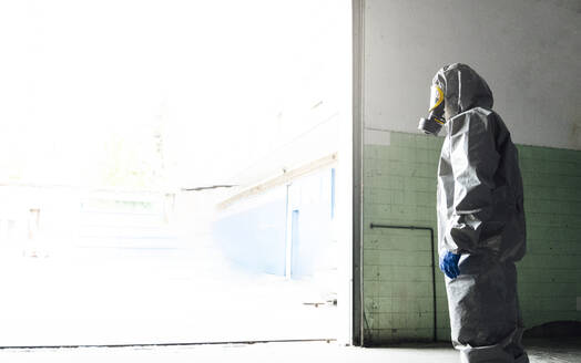 Side view of sanitation worker standing in protective workwear at warehouse entrance - JCMF00674