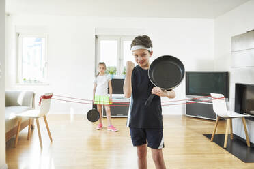 Boy winning while playing tennis with sister in living room at home - DIKF00470