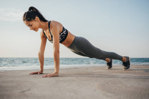 Full length of young woman doing push-ups on promenade - OYF00129
