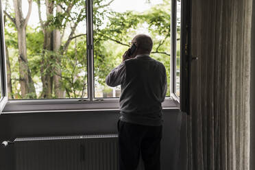 Back view of senior man on the phone standing at open window - UUF20222