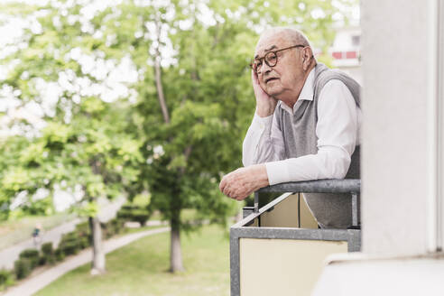 Portrait of senior man standing on balcony looking at distance - UUF20228