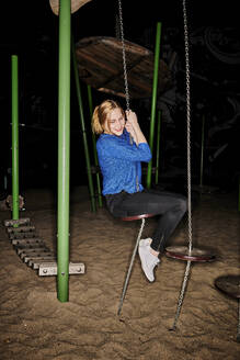 Full length of happy young woman playing in playground at night - MMIF00262