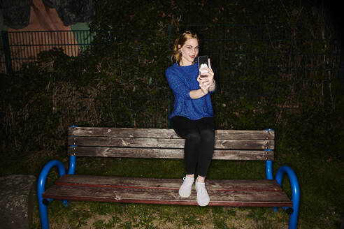 Portrait of young woman taking selfie while sitting on bench in park at night - MMIF00265