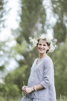 Smiling pregnant woman wearing flowers standing in park - EYAF01056