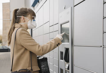 Woman wearing face mask and gloves using parcel terminal - AHSF02448
