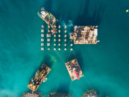 Aerial view of machinery on concrete platforms at the construction of future LNG terminal on the shore of the bay in Omisalj, Croatia - AAEF08207