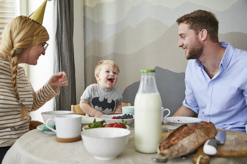 Portrait of little boy having fun with his parents at breakfast table - FSF01052