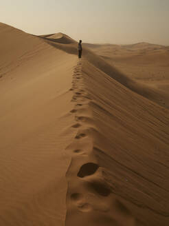 Woman on the ridge of a dune in the desert, Walvis Bay, Namibia - VEGF02071