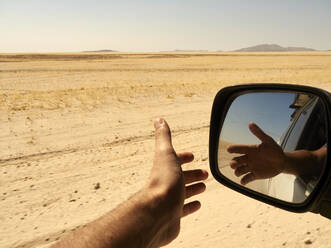 Reflection in the rear view mirror of a man's hand outside the window while driving in the desert, Sossusvlei, Namibia. - VEGF02086