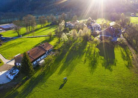 Germany, Bavaria, Gaissach, Drone view of sunlight illuminating countryside farmhouses - SIEF09809