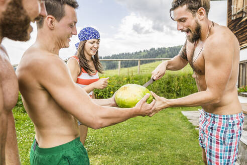 Friends sharing a watermelon on a meadow in the mountains, Achenkirch, Austria - SDAHF00867