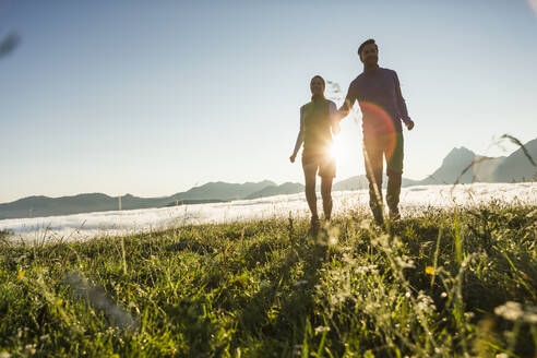 Couple hiking on a meadow in the mountains at sunrise, Achenkirch, Austria - SDAHF00882