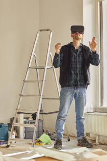 Man refurbishing shop location, using VR glasses - MCF00783