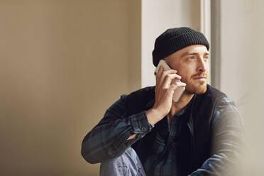 Man refurbishing shop location, sitting on windowsill, talking on the phone - MCF00795