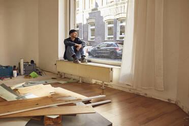 Man refurbishing shop location, sitting on windowsill - MCF00798