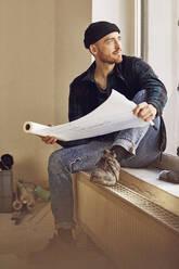 Man refurbishing shop location, sitting on windowsill, studying blueprint - MCF00804