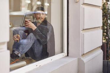 Man refurbishing shop location, sitting on windowsill, drinking coffee - MCF00807