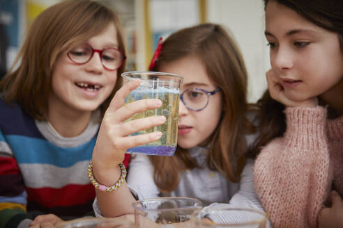 Three children looking at liquid in a science chemistry lesson - PWF00073