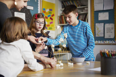 Three children and teacher during a science lesson - PWF00097