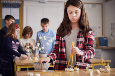 Girl setting up construction during a science lesson - PWF00103