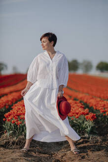 Portrait of fashionable woman dressed in white standing in front of tulip field - OGF00348