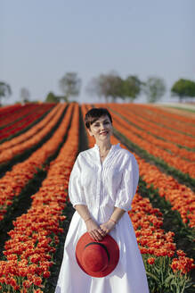 Portrait of smiling woman dressed in white standing in front of tulip field - OGF00351