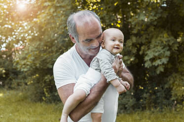 Smiling senior man holding baby girl on his arm in a park - DIGF10243