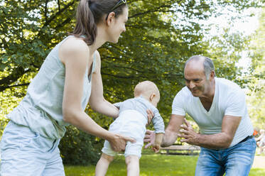 Senior man spending time with his adult daughter and his granddaughter in a park - DIGF10246