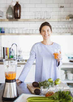 Portrait smiling, confident brunette woman drinking healthy carrot juice at blender in kitchen - CAIF27011