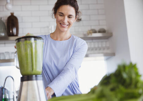 Smiling woman making healthy green smoothie in blender in kitchen - CAIF27035