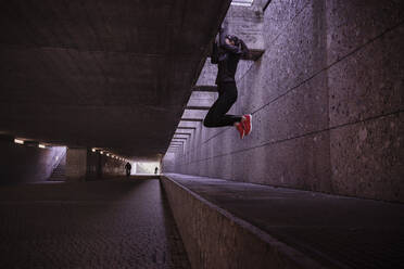 Female athlete working out in a pedestrian underpass, doing chin-ups - DHEF00179