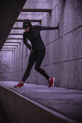 Female athlete warming up before running in pedestrian underpass - DHEF00182