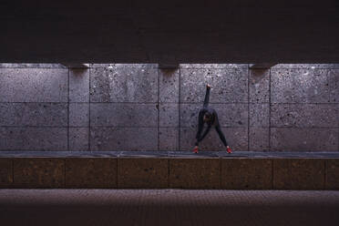 Female athlete warming up before running in pedestrian underpass - DHEF00185