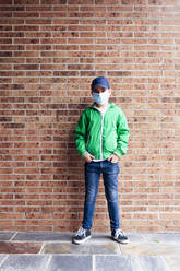 Boy wearing protective mask standing in front of a brick wall - JCMF00680