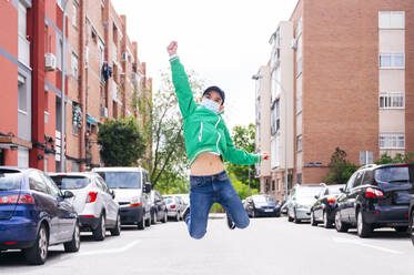 Boy wearing protective mask and jumping on a street - JCMF00683
