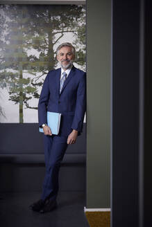 Portrait of confident mature businessman holding folder in office - RBF07641