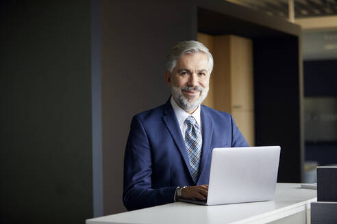 Portrait of mature businessman using laptop in office - RBF07656