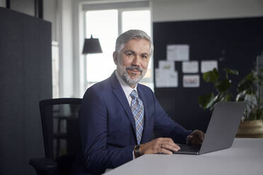 Portrait of mature businessman using laptop in office - RBF07668