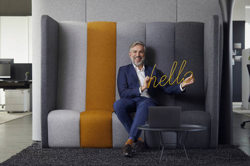 Portrait of smiling mature businessman sitting on couch in office holding hello sign - RBF07677