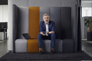 Portrait of mature businessman sitting on couch in office - RBF07680