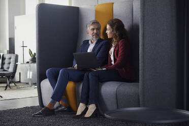 Businesswoman and businessman sitting on couch in office sharing laptop - RBF07683