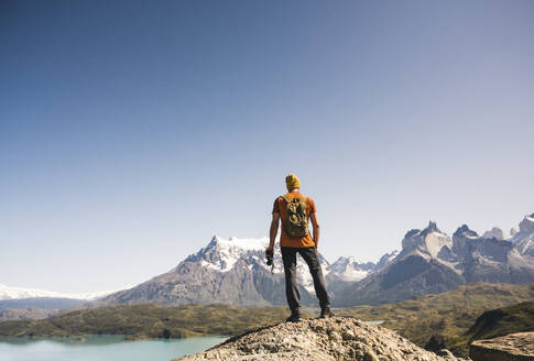 Hiker in mountainscape at Lago Pehoe in Torres del Paine National Park, Patagonia, Chile - UUF20237